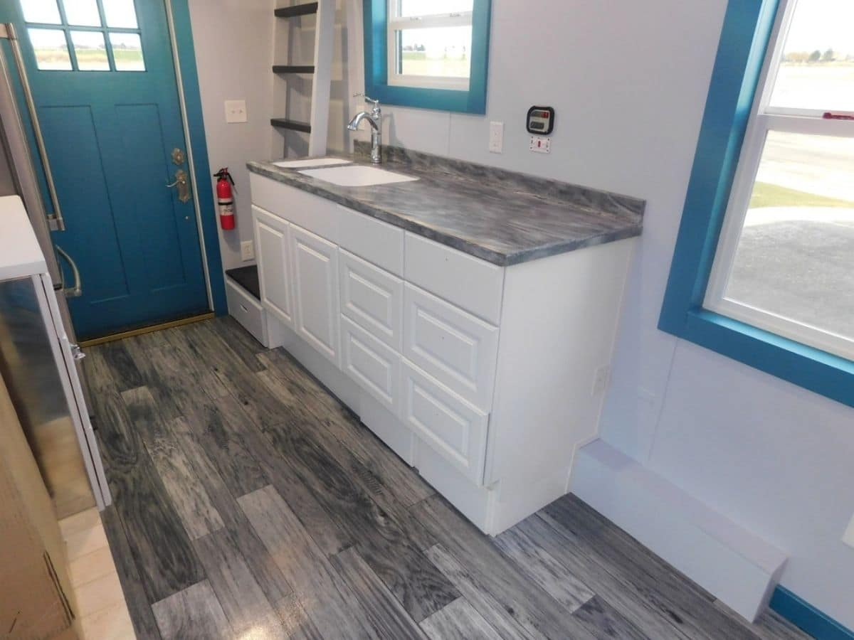 Gray wood floors and white cabinets next to teal trim on windows