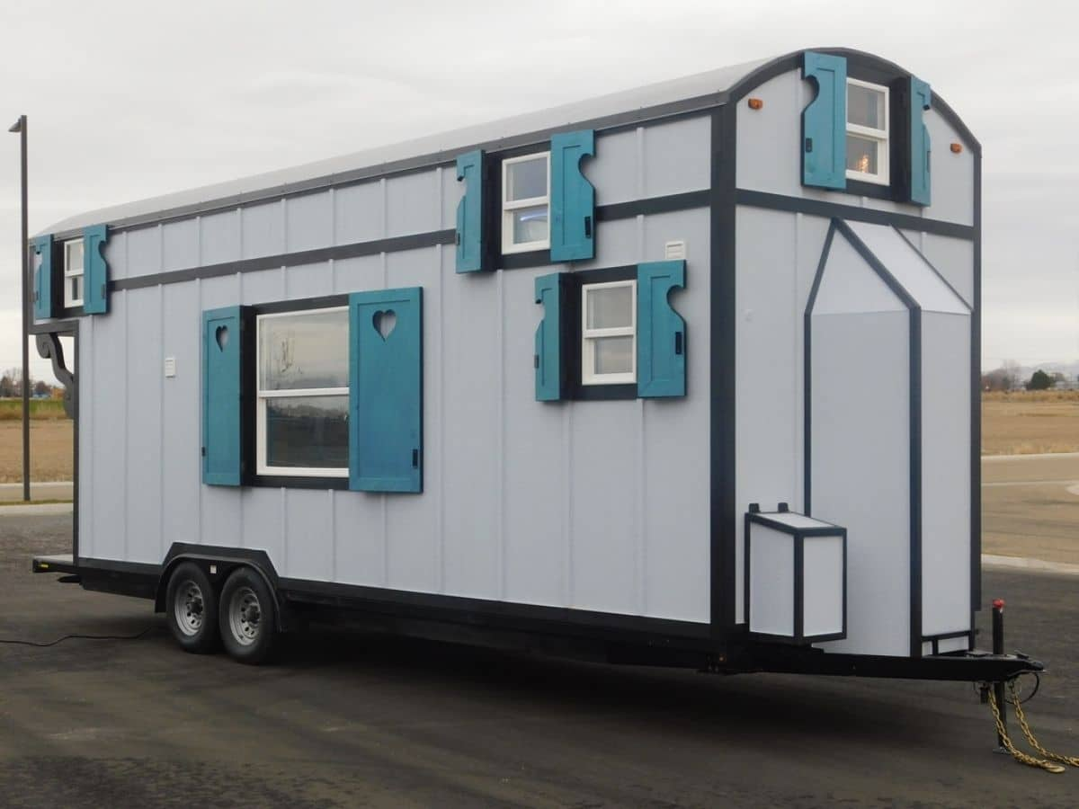 White and teal tiny home on wheels on lot