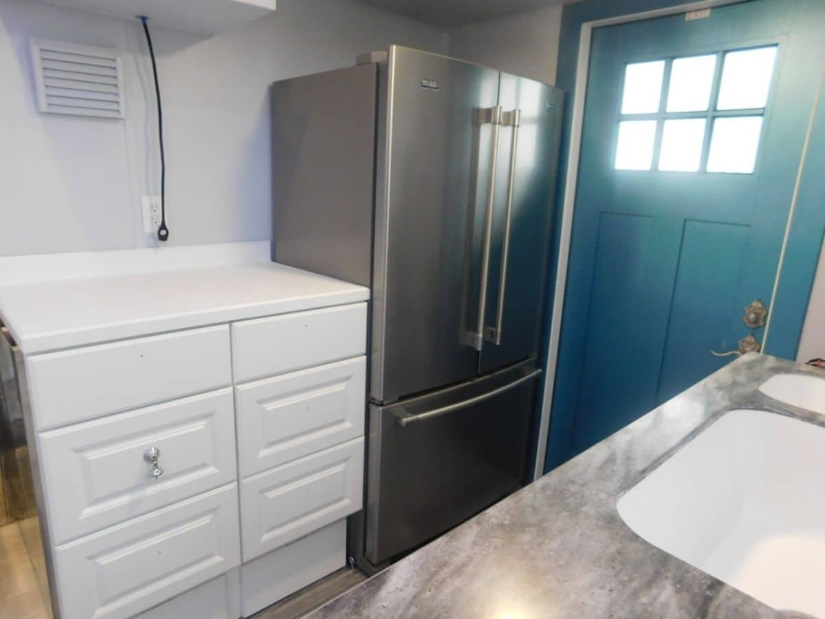 Stainless steel refrigerator with french doors next to teal door in home