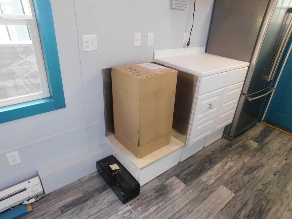 Box on top of cabinet in tiny home with white cabinets