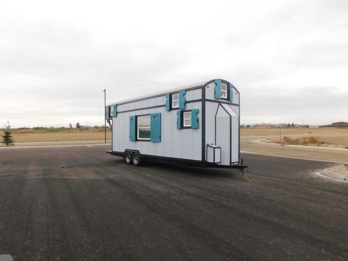 Tiny home with white siding parked in lot