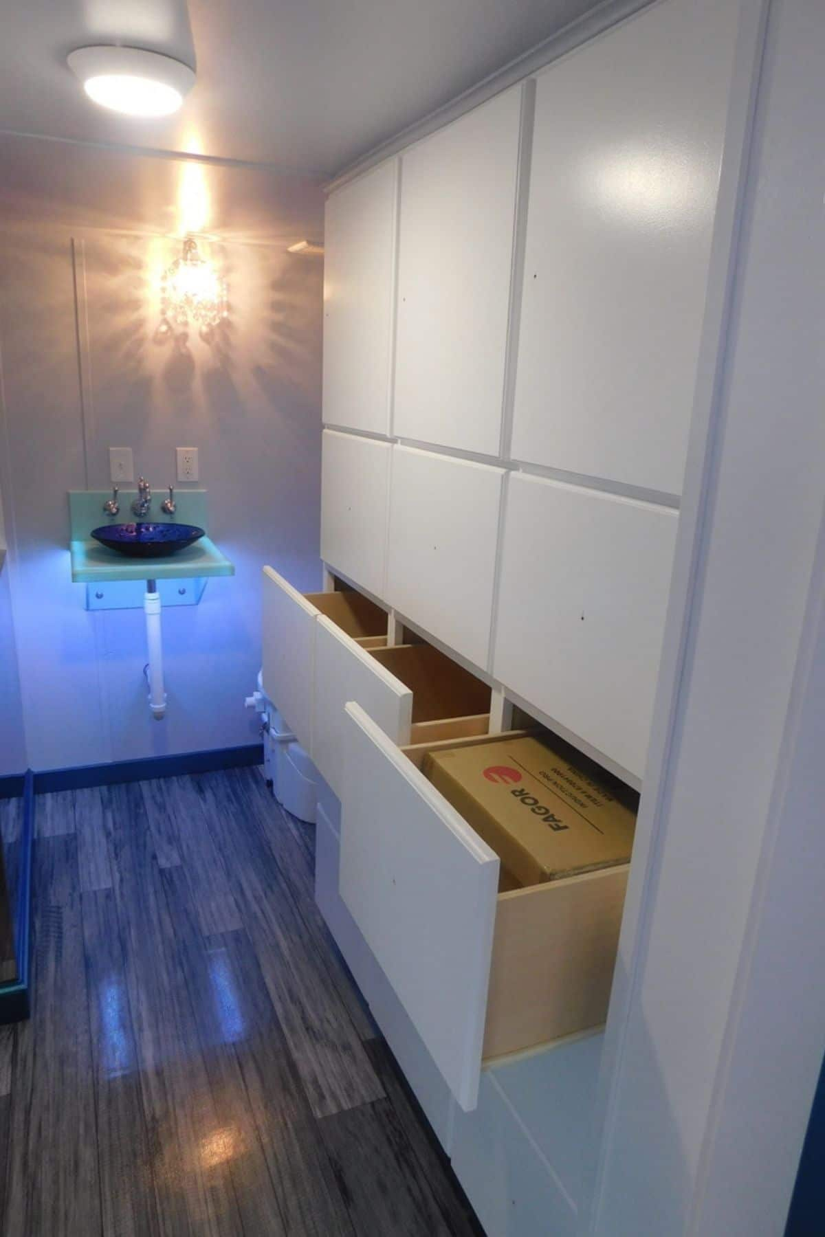 Wall of white drawers in bathroom