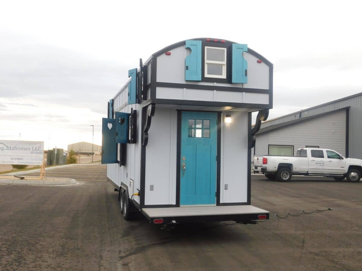 Teal front door on tiny home parked in lot