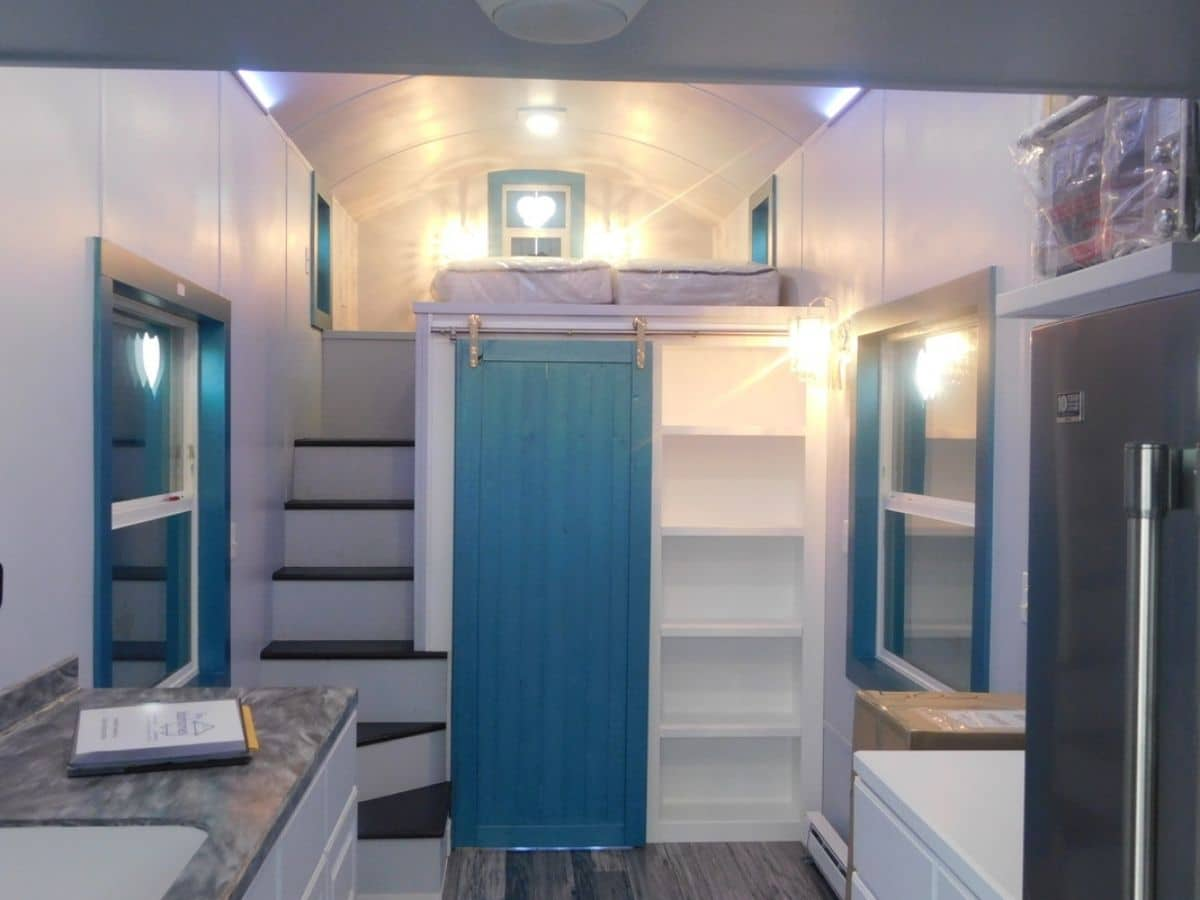 View into tiny home with teal door next to loft stairs