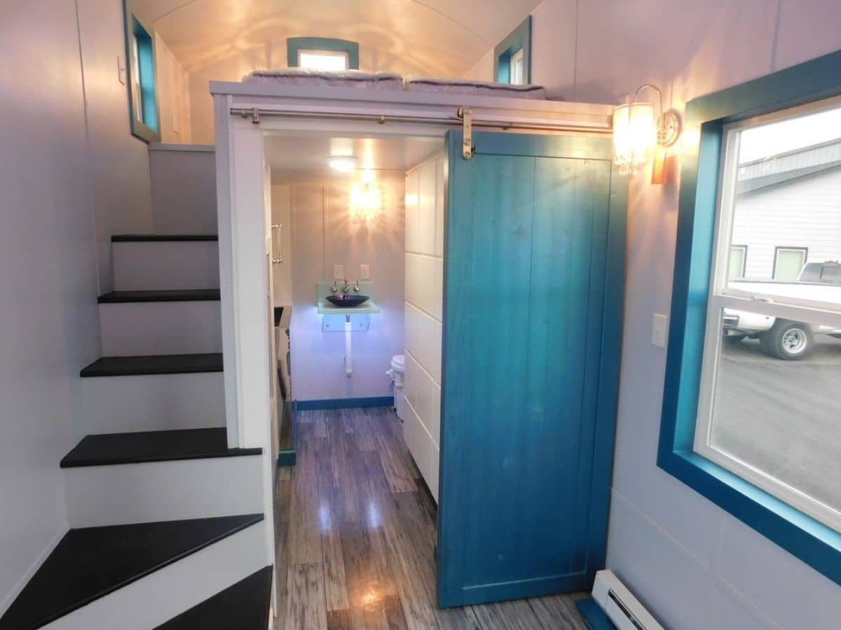 Teal door to bathroom open with stairs to left leading to loft