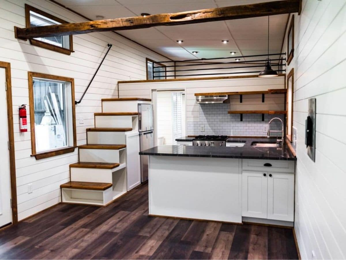 Dark wood floors in space with white walls and stairs to loft