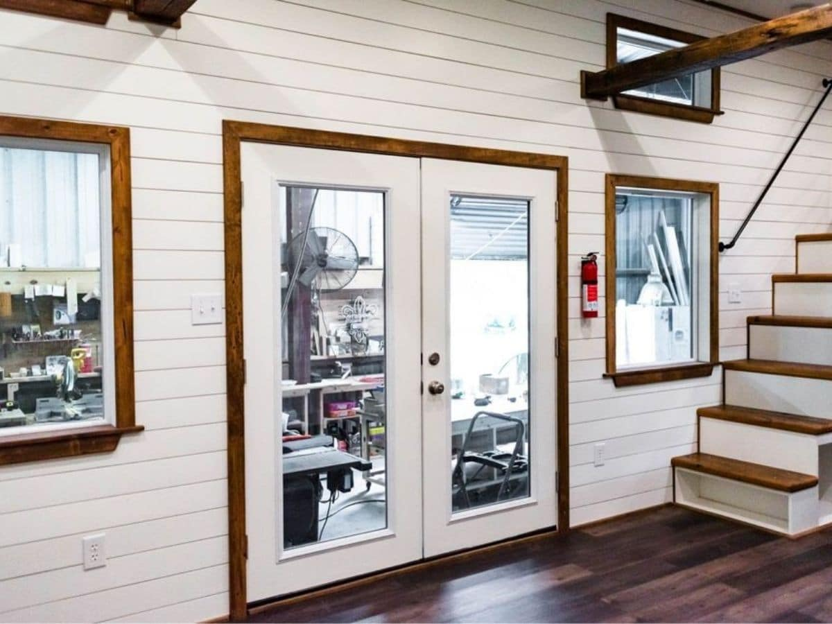 French doors with white and wood trim in white shiplap wall