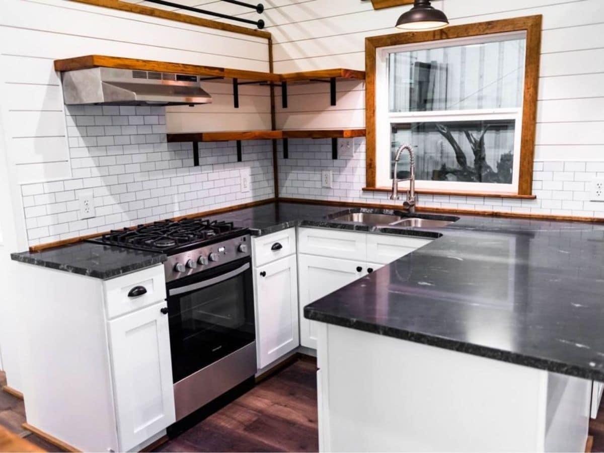 Black counters on top of white cabinets in kitchen
