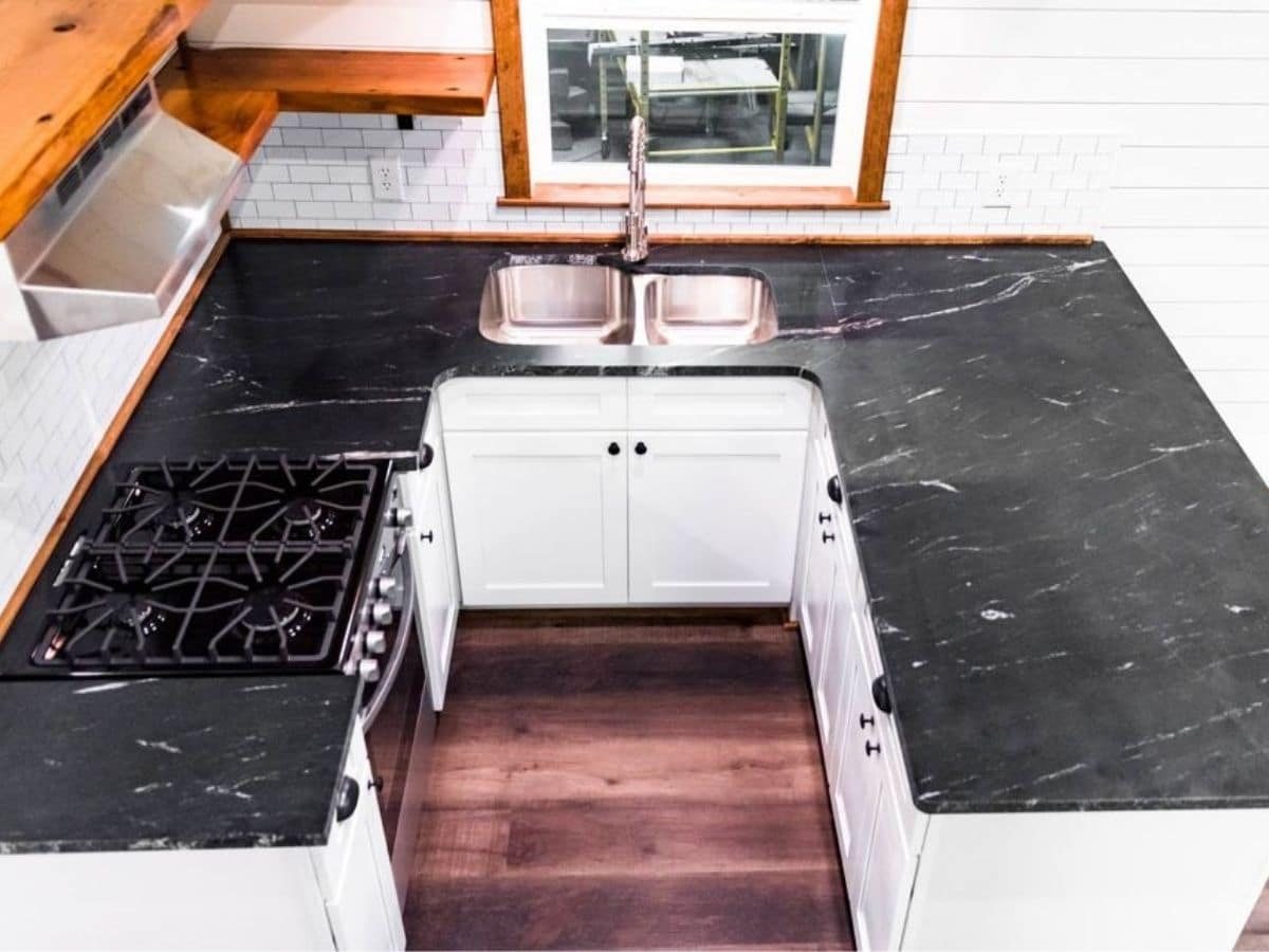 U shaped kitchen with white cabinets and white counters