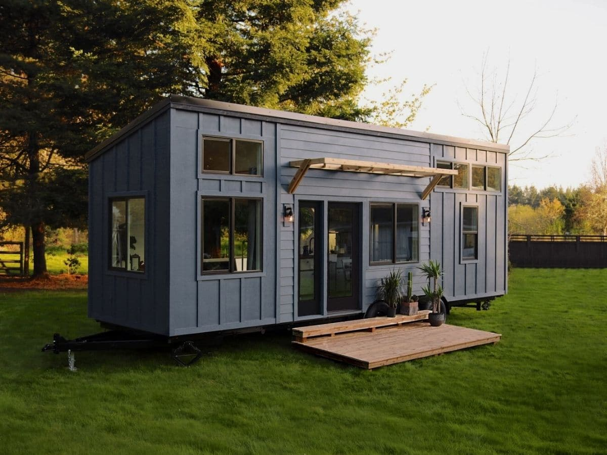 Light gray tiny house with awning over doors