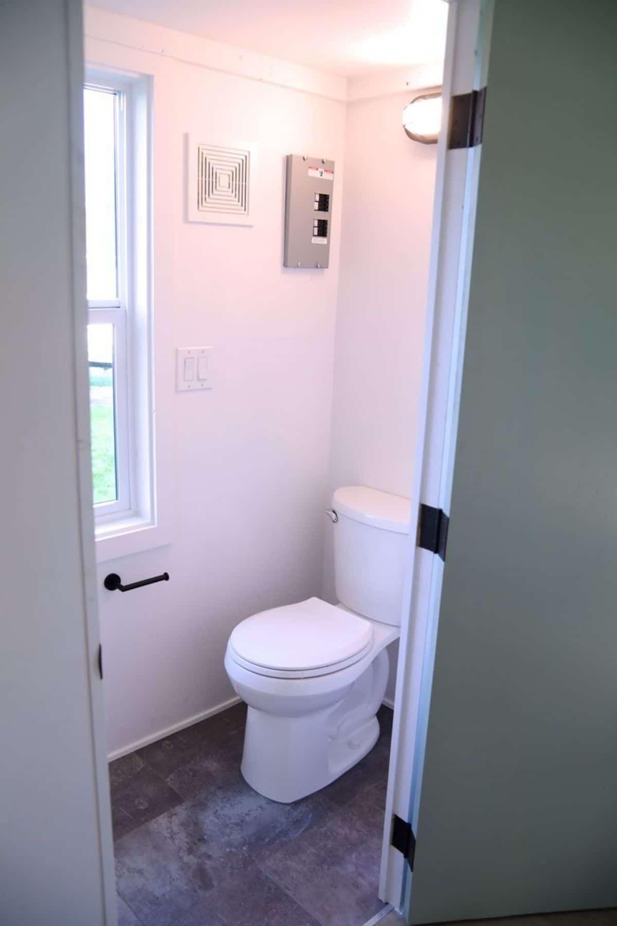 White flush toilet against wall in bathroom