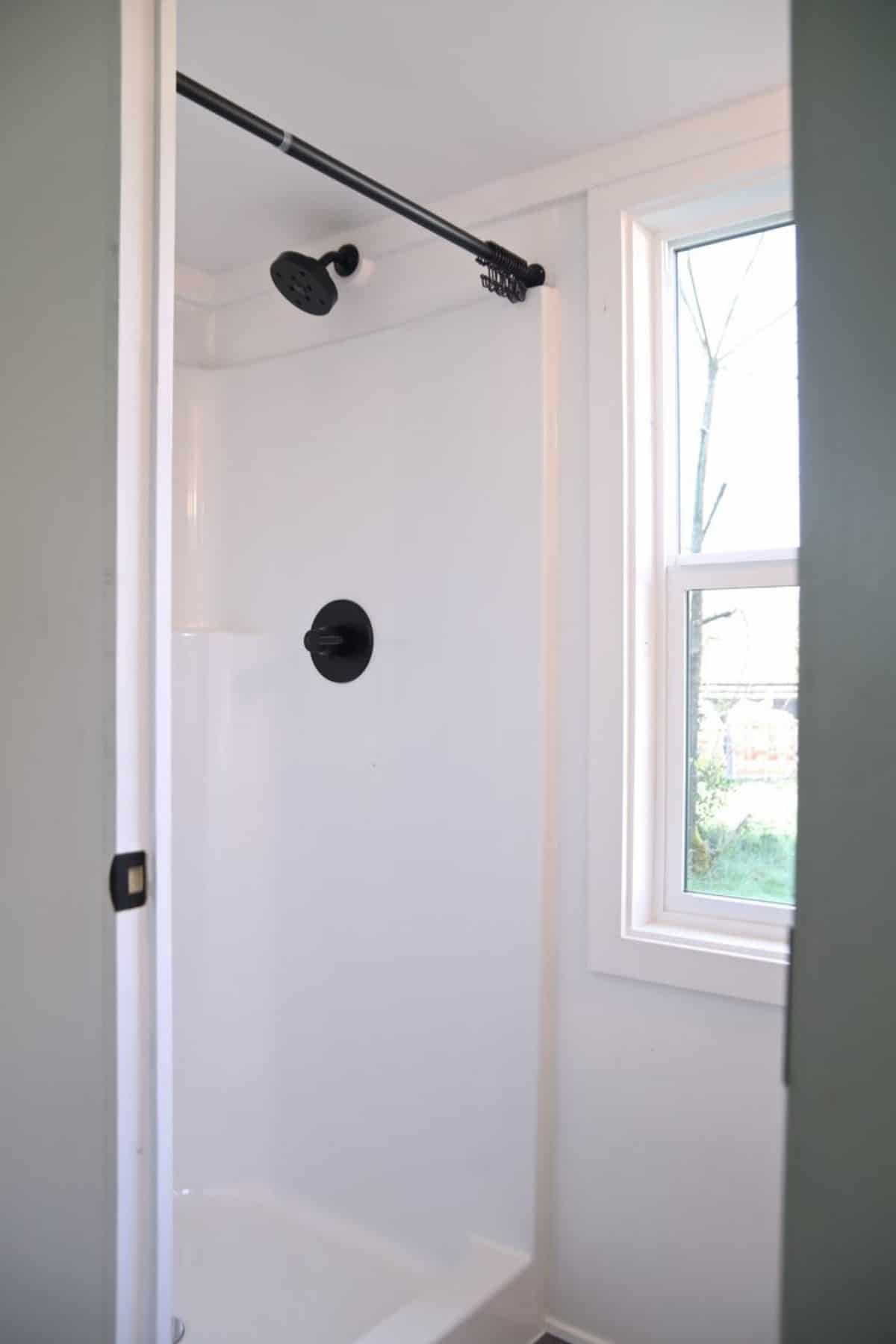 White shower stall with black faucets