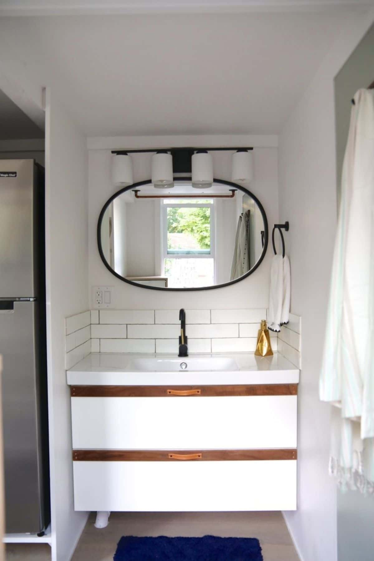 White vanity with wood trim on drawers and oval mirror above