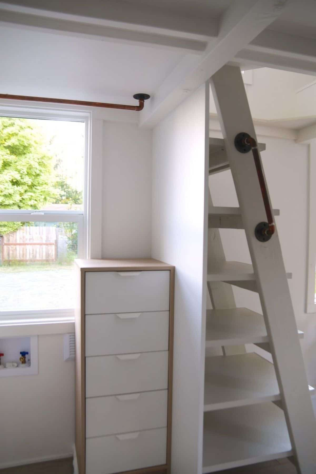 Small cabinet behind stiars to loft