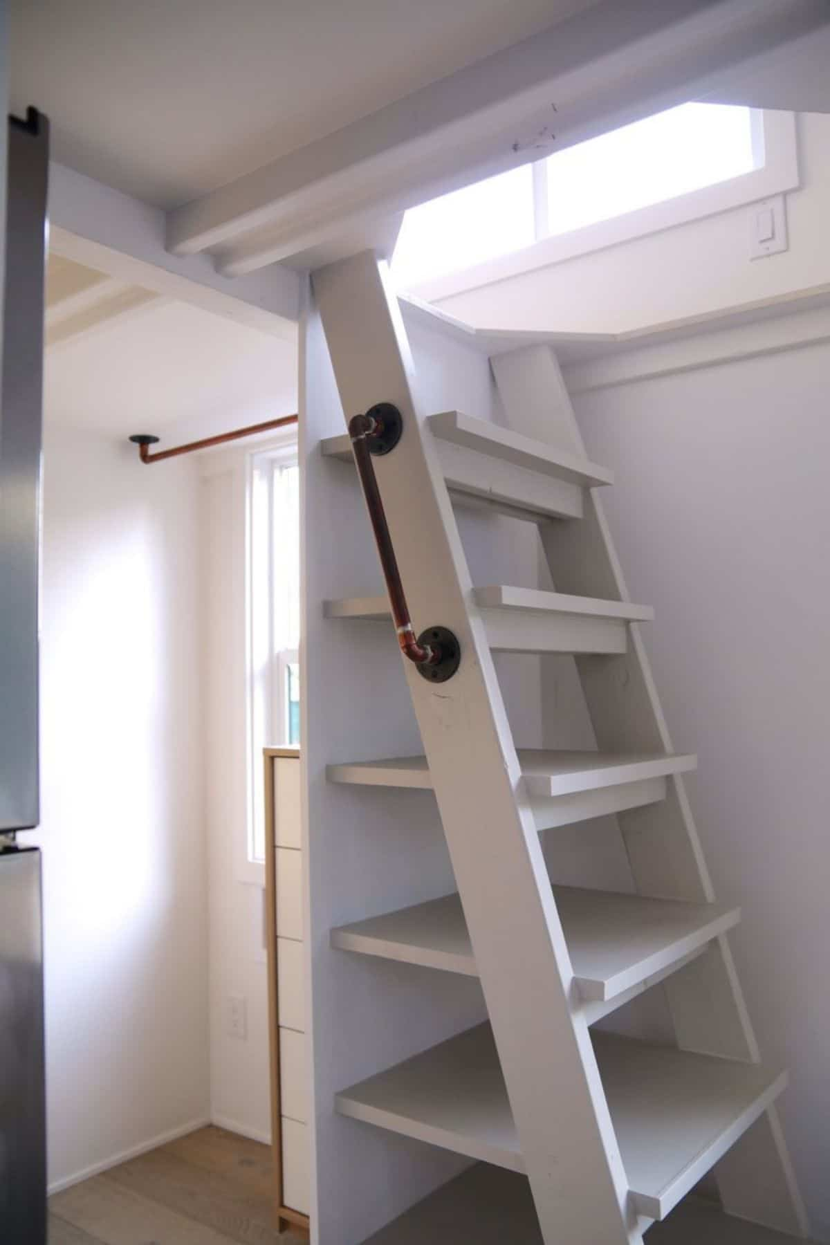 White stairs to loft with deep storage