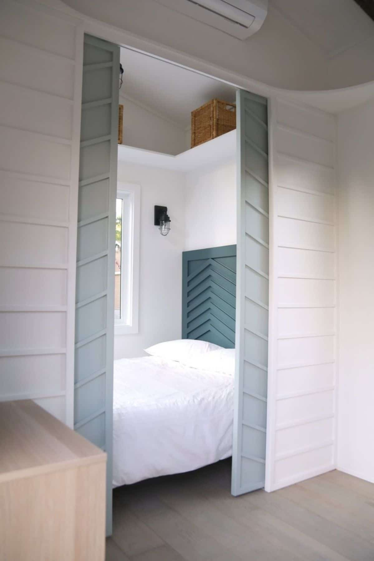 Open blue doors looking into tiny bedroom with blue headboard and white bed