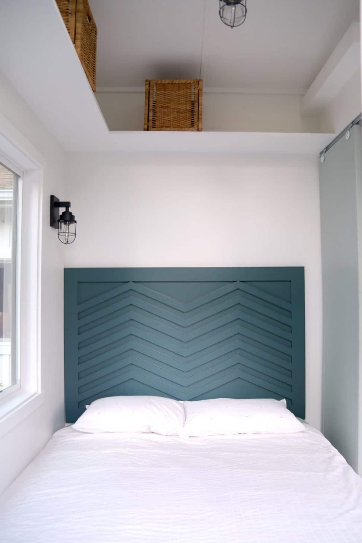 Teal headboard on twin bed in tiny bedroom