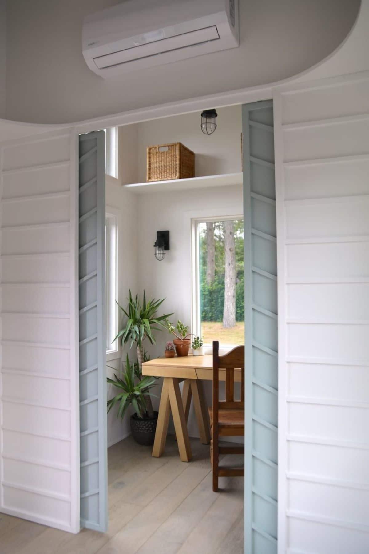 Open blue doors showing desk against window in tiny room
