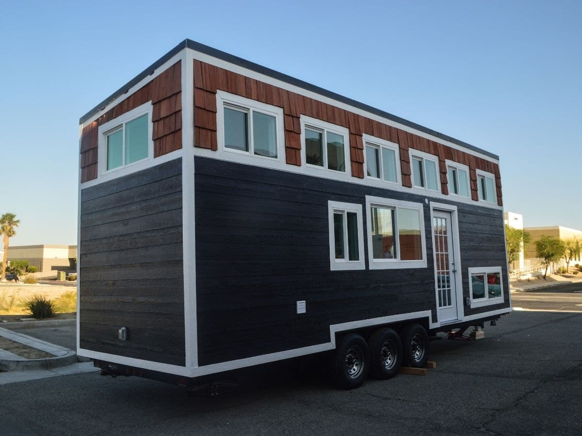 Blue tiny home with wood upper half and white trim sitting on lot