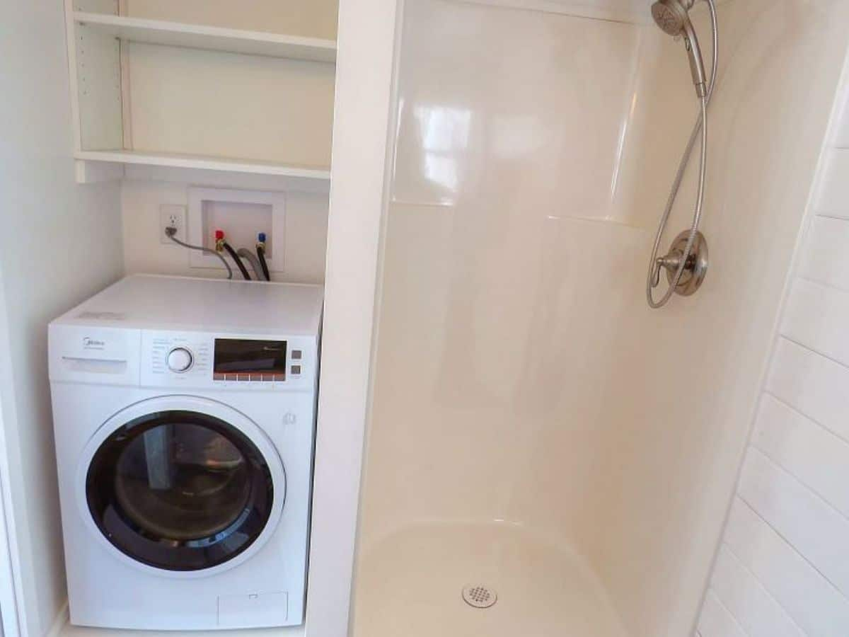 Shower stall with washing machine in nook beside it below shelves