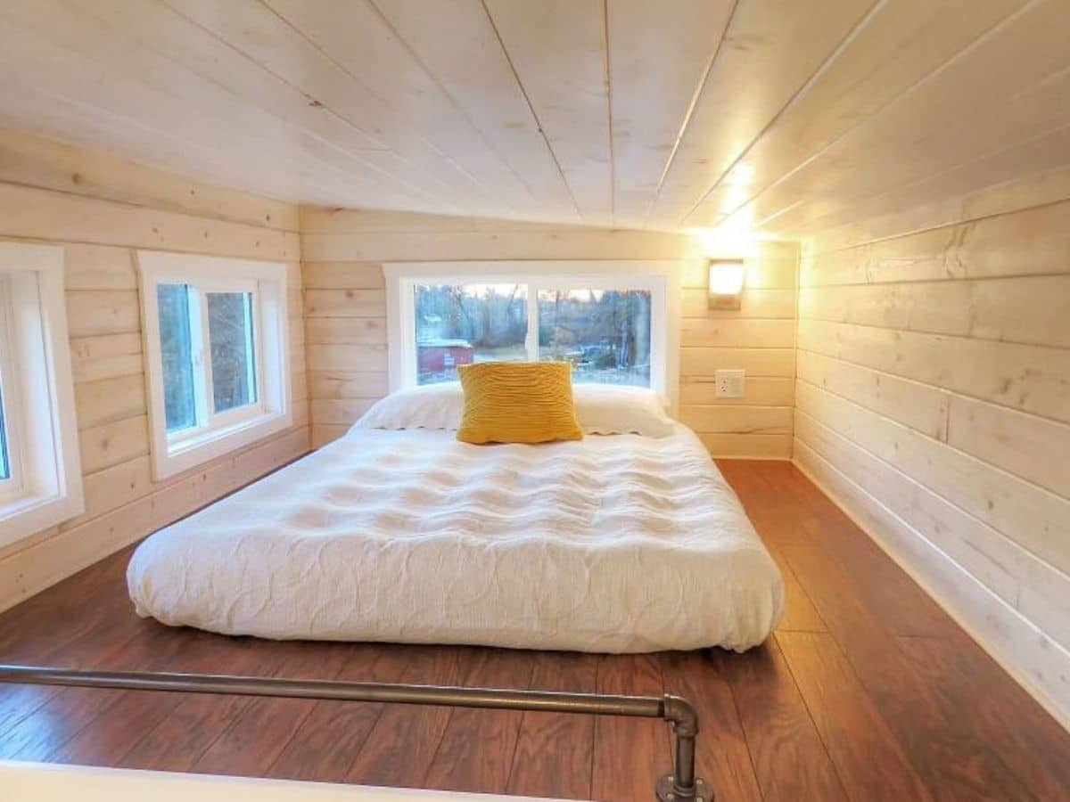 Bed with white bedding and yellow pillow in loft