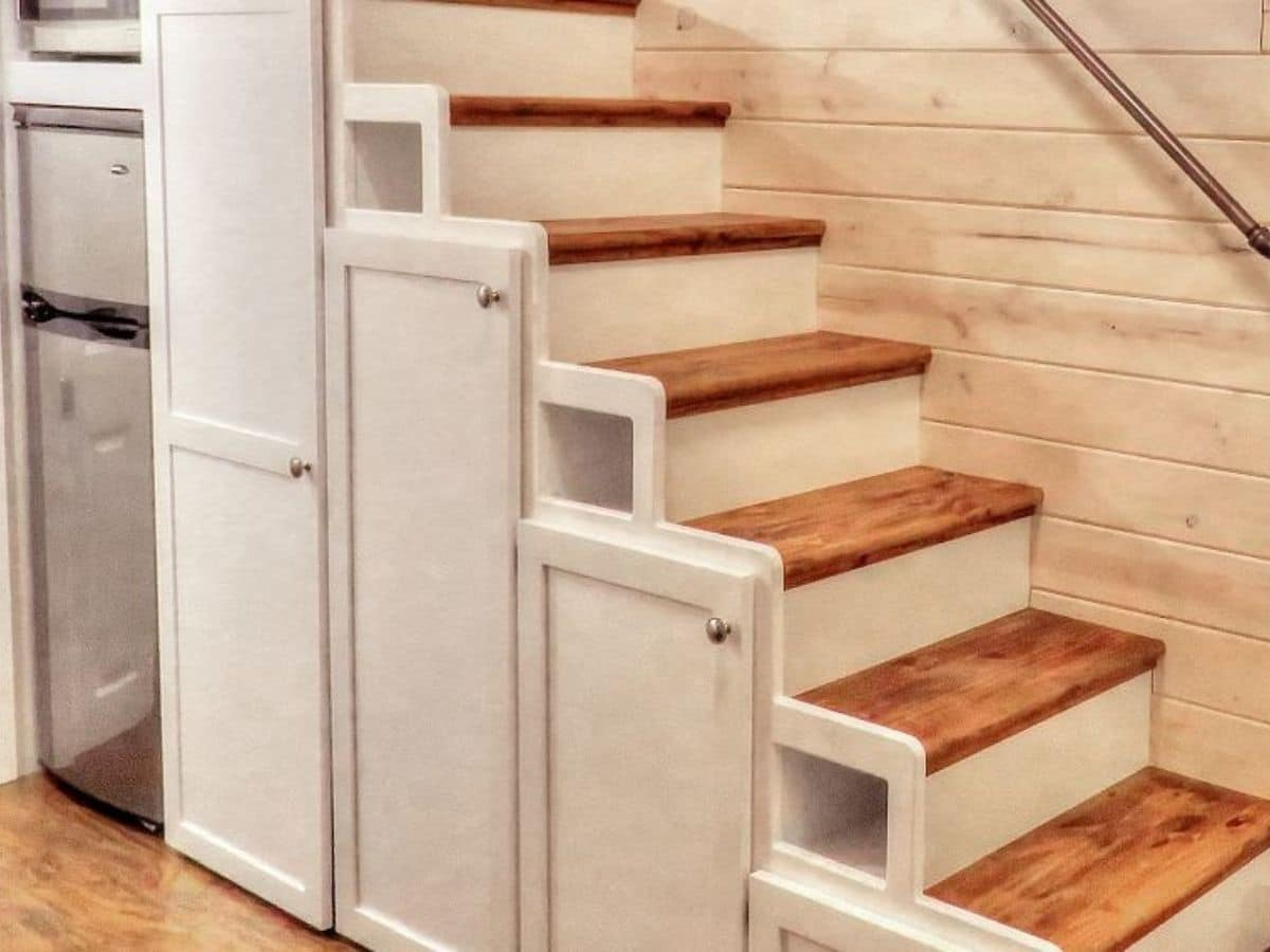 white cabinet doors on stairs with stained wood steps