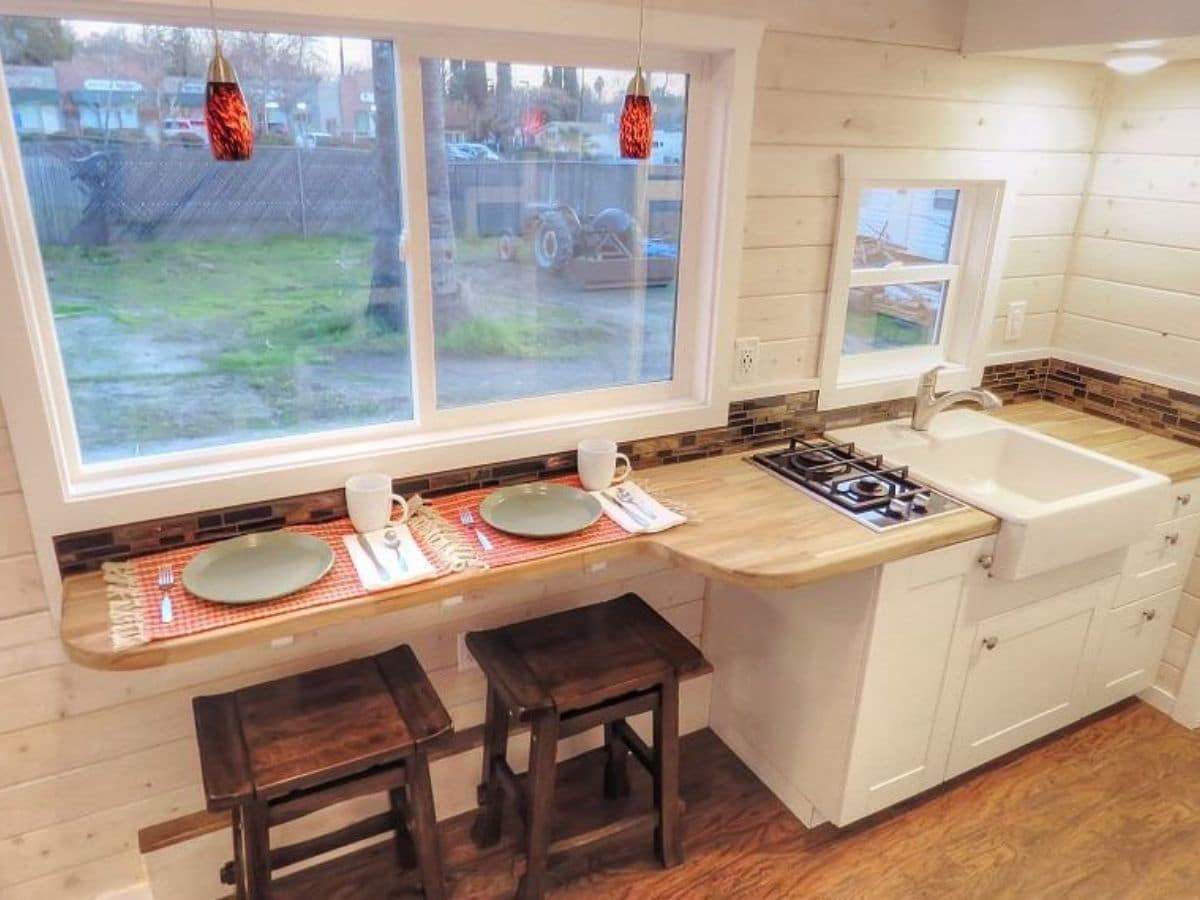 Kitchen counter with stools beneath under two large windows