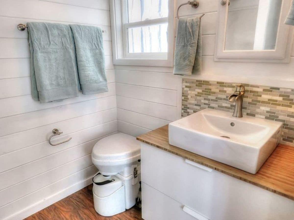 Toilet next to white vanity with white bowl sink