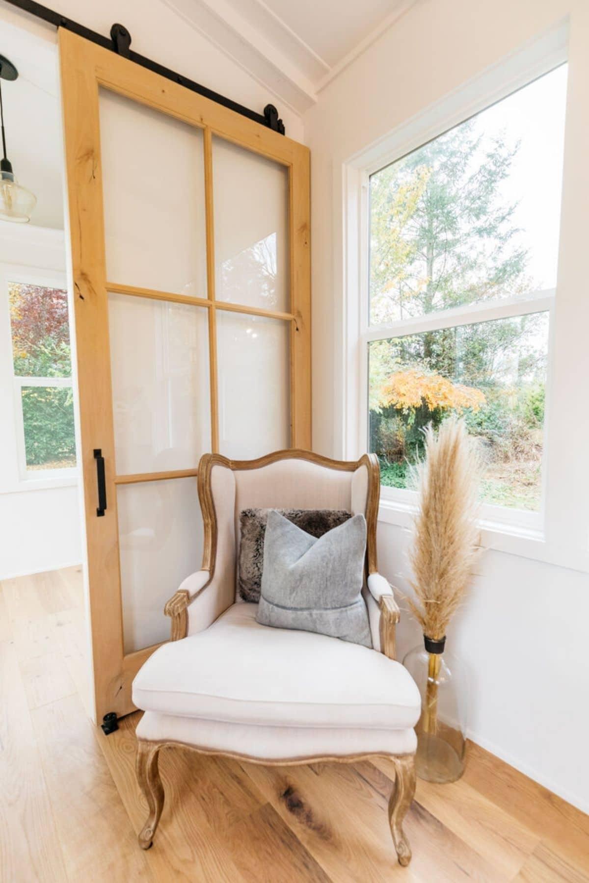 Chair in corner by window and glass pane barn door