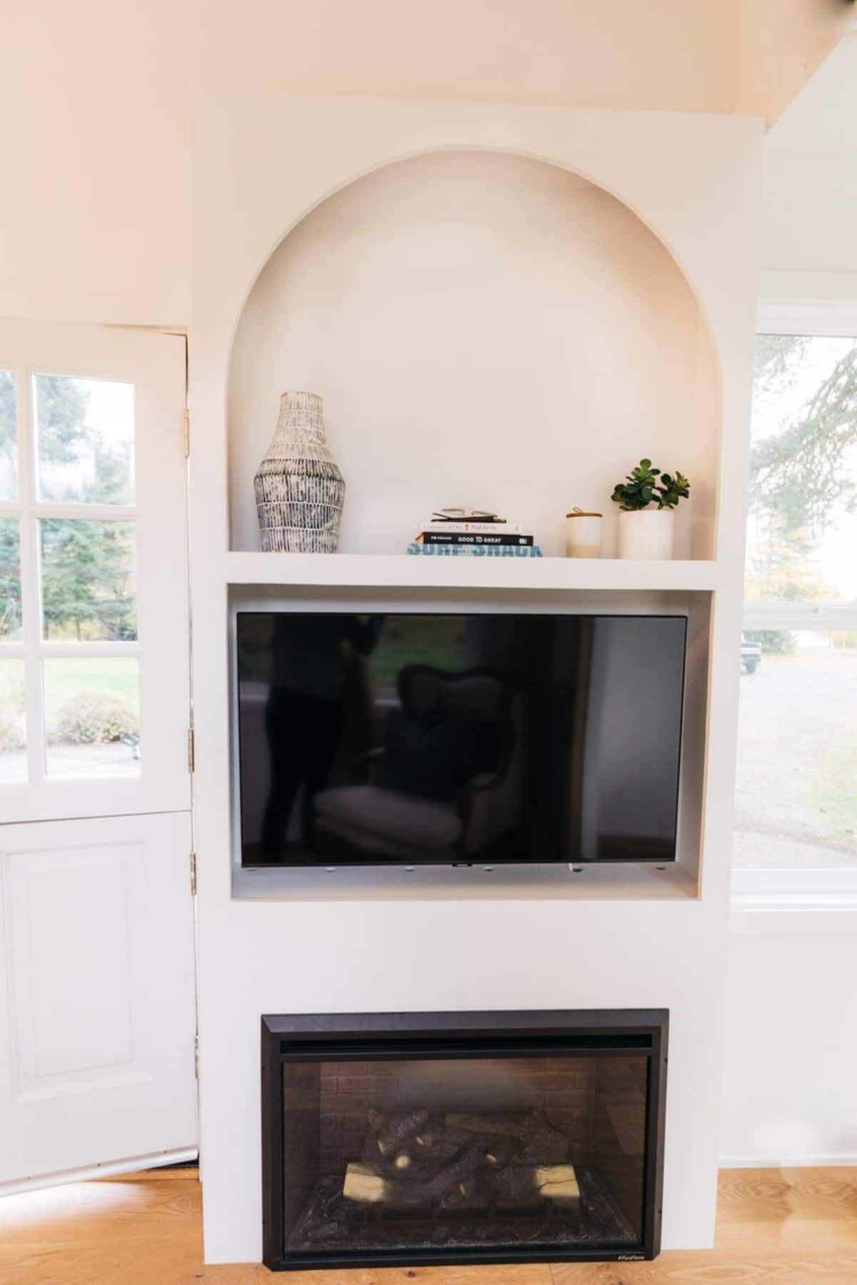 TV in wall cubby with fireplace below