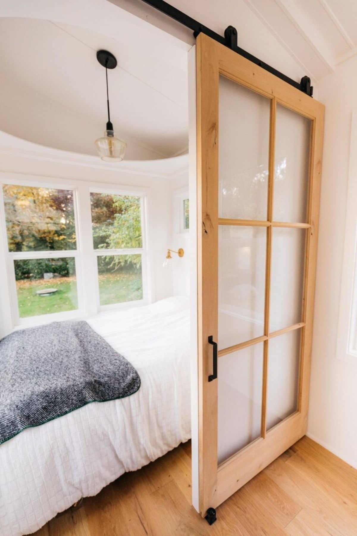 Bed behind glass pane barn door