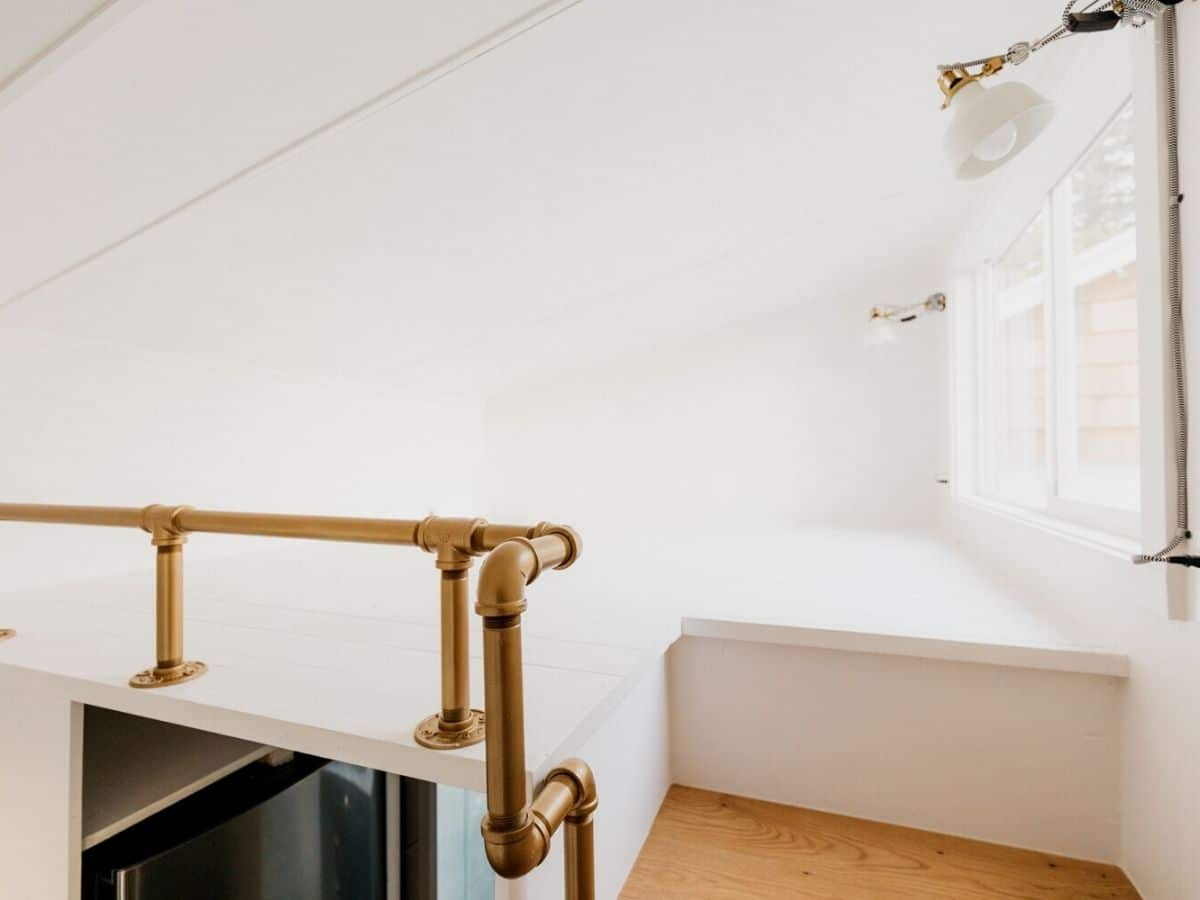 Loft with white floor and walls and brass railing