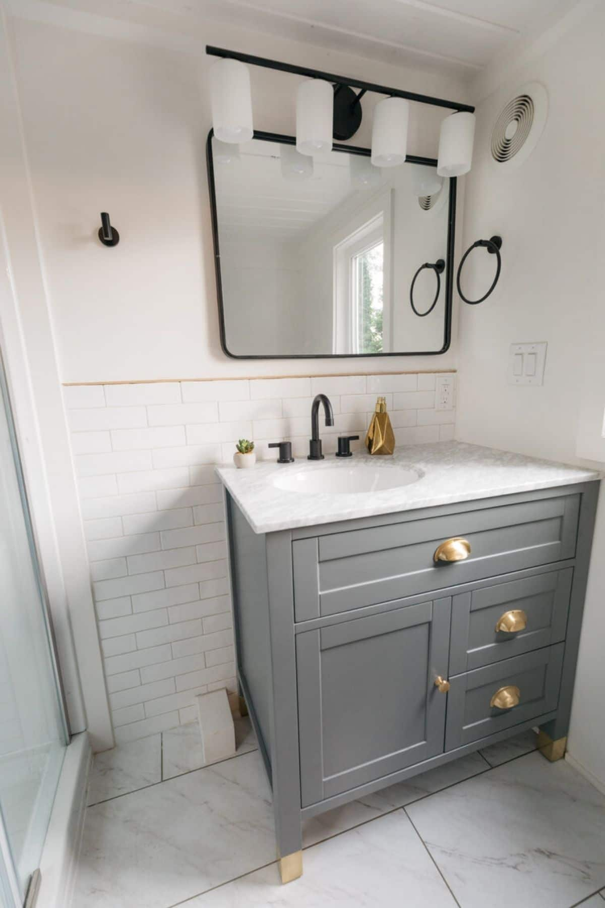 Gray cabinet under white sink against white wall