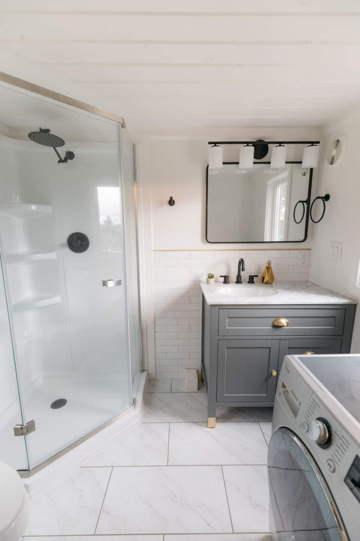 Bathroom with washing machine in foreground and corner glass shower in background