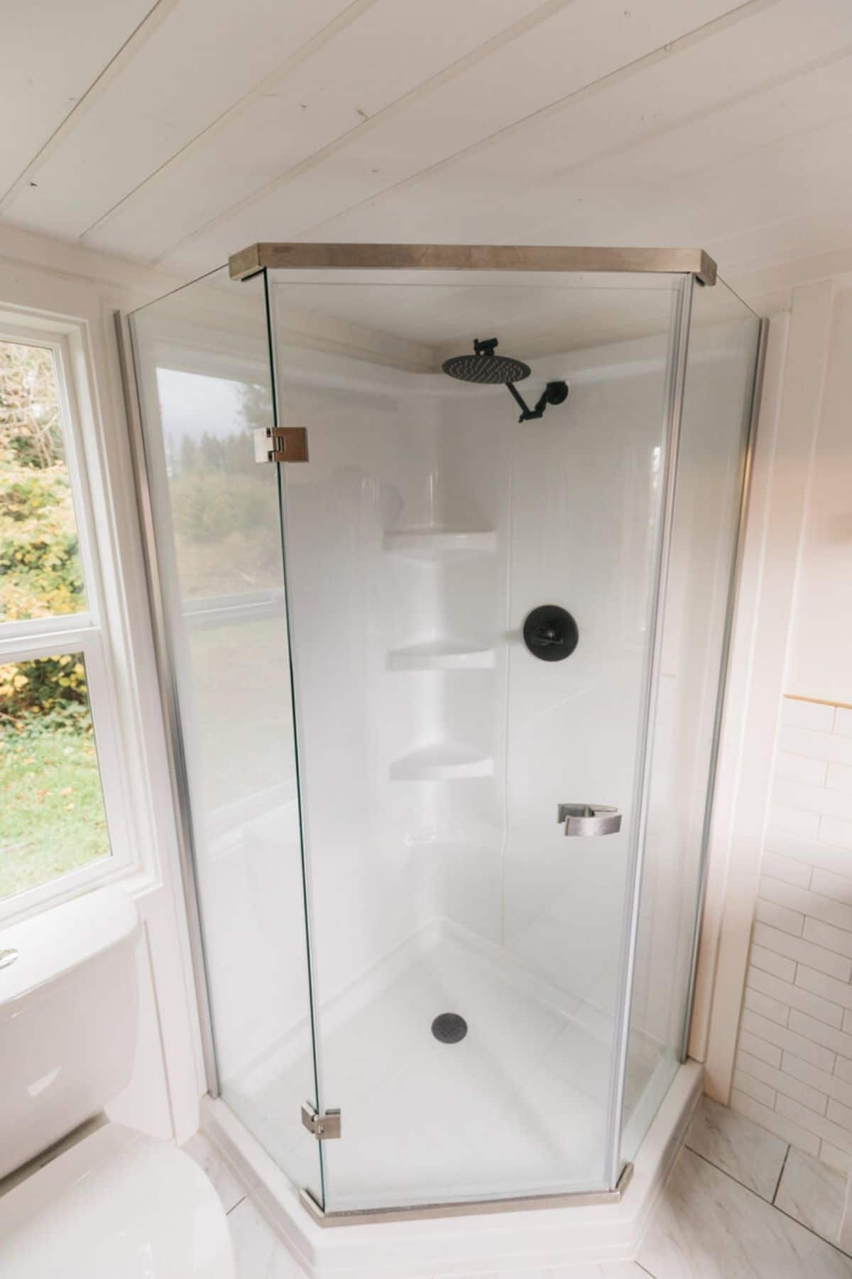 Corner shower with glass doors against wall with window