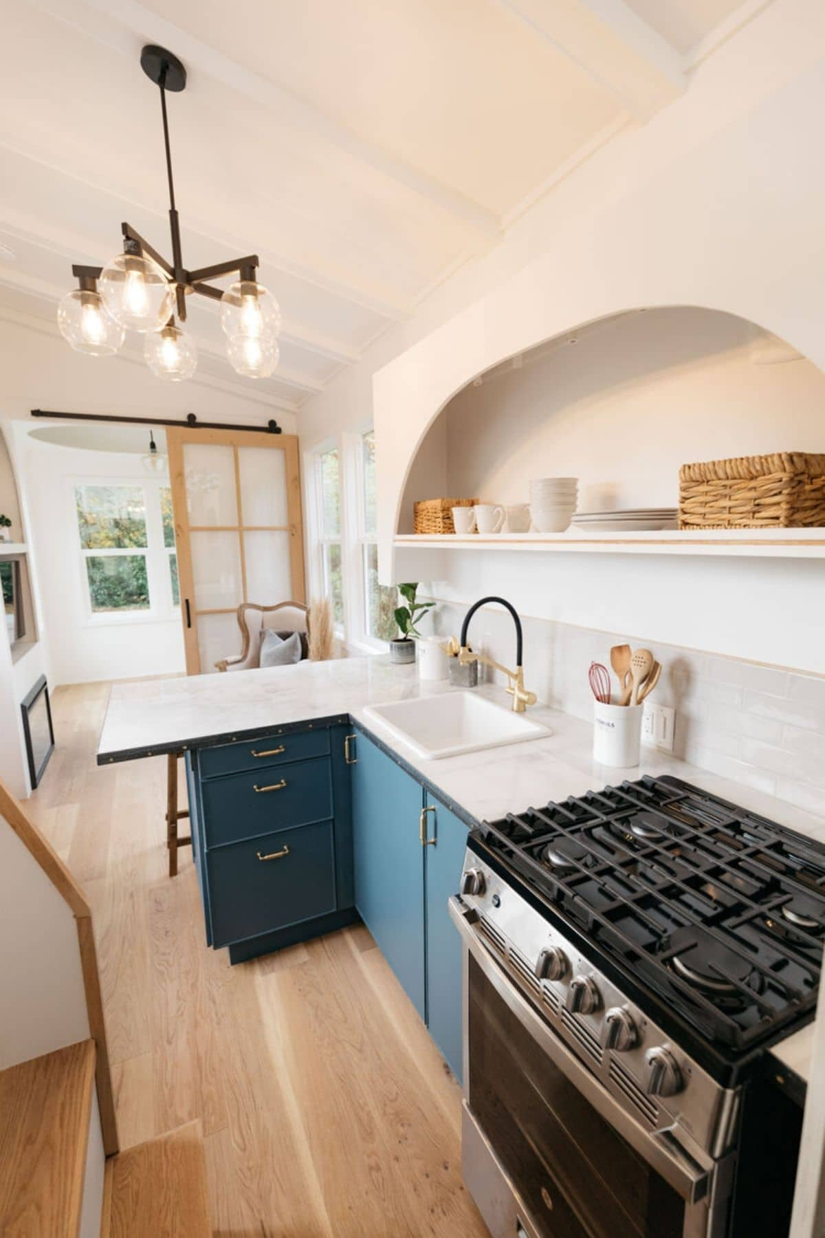 Teal cabinets under white counter with gas stove in foreground