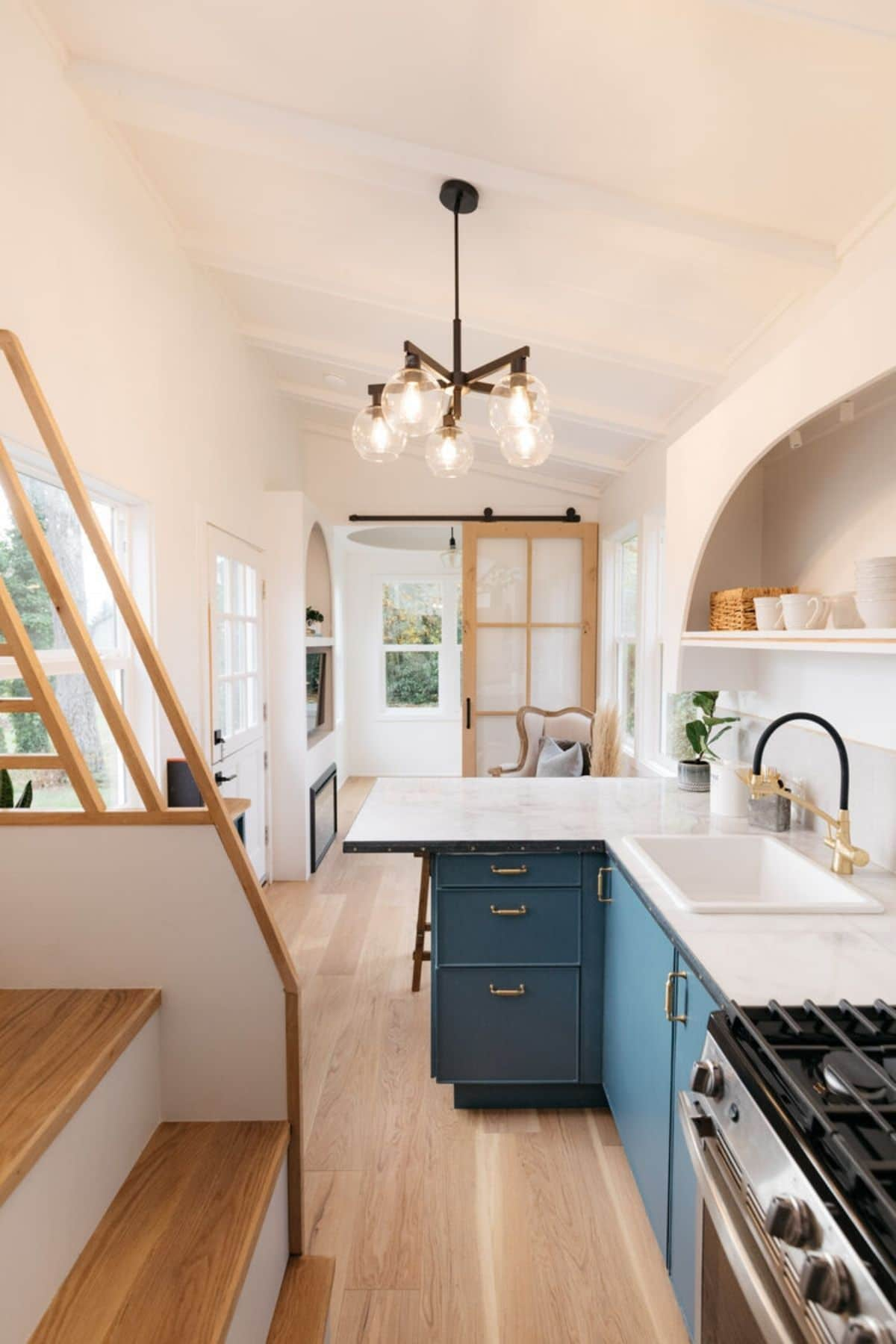 View from kitchen into tiny home living area with edison light chandelier