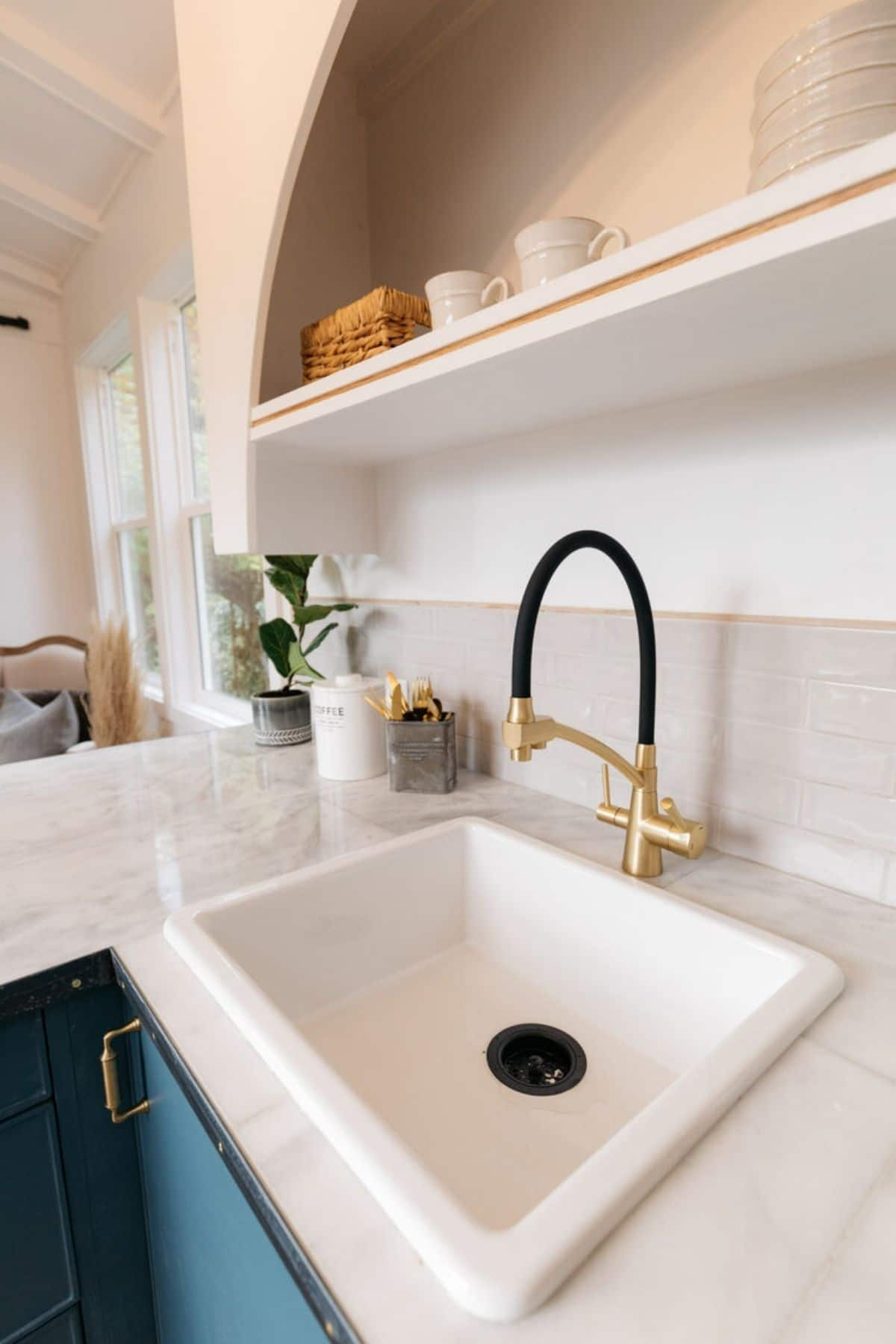 Deep white farmhouse sink with black and brass faucet
