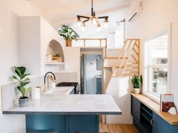 Teal cabinets in kitchen of tiny home with wood stools in foreground