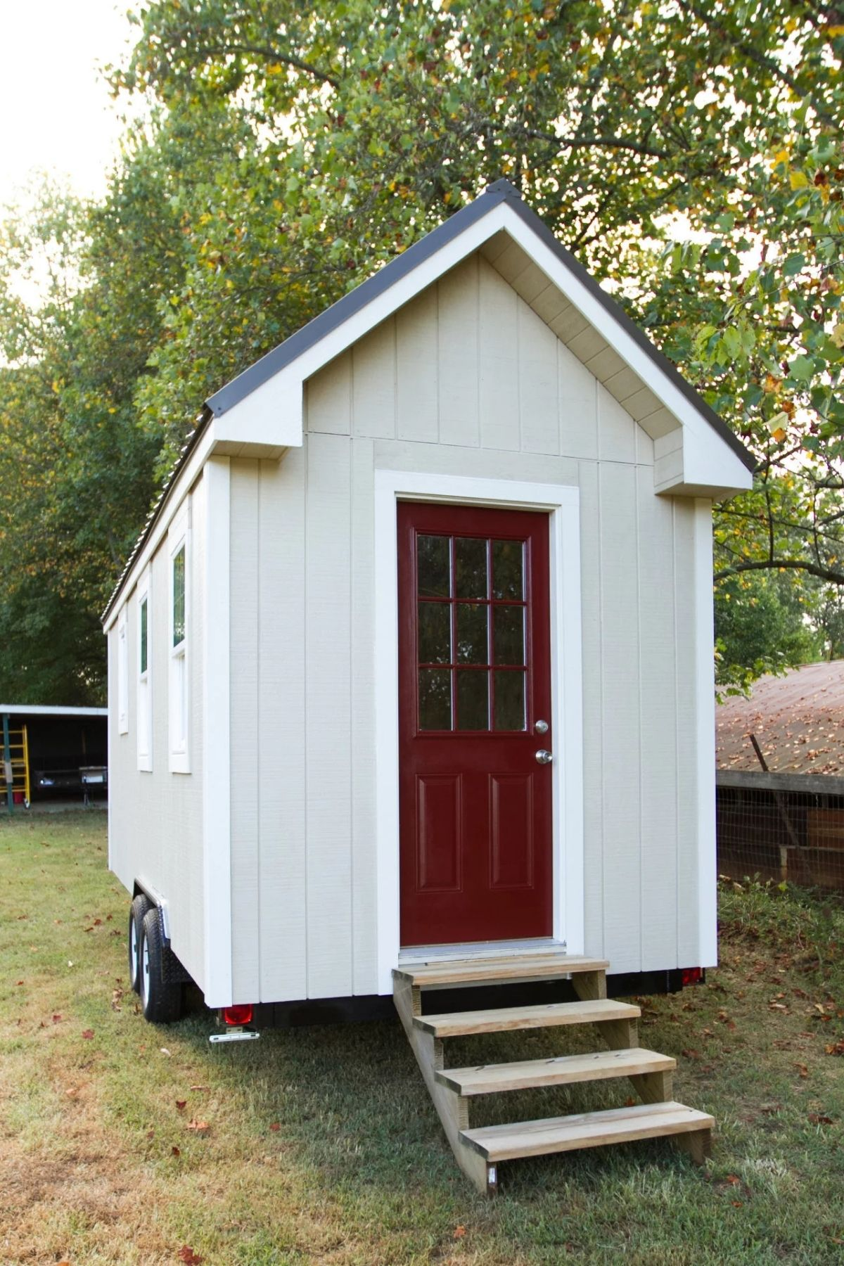 White tiny home with wood steps and red door