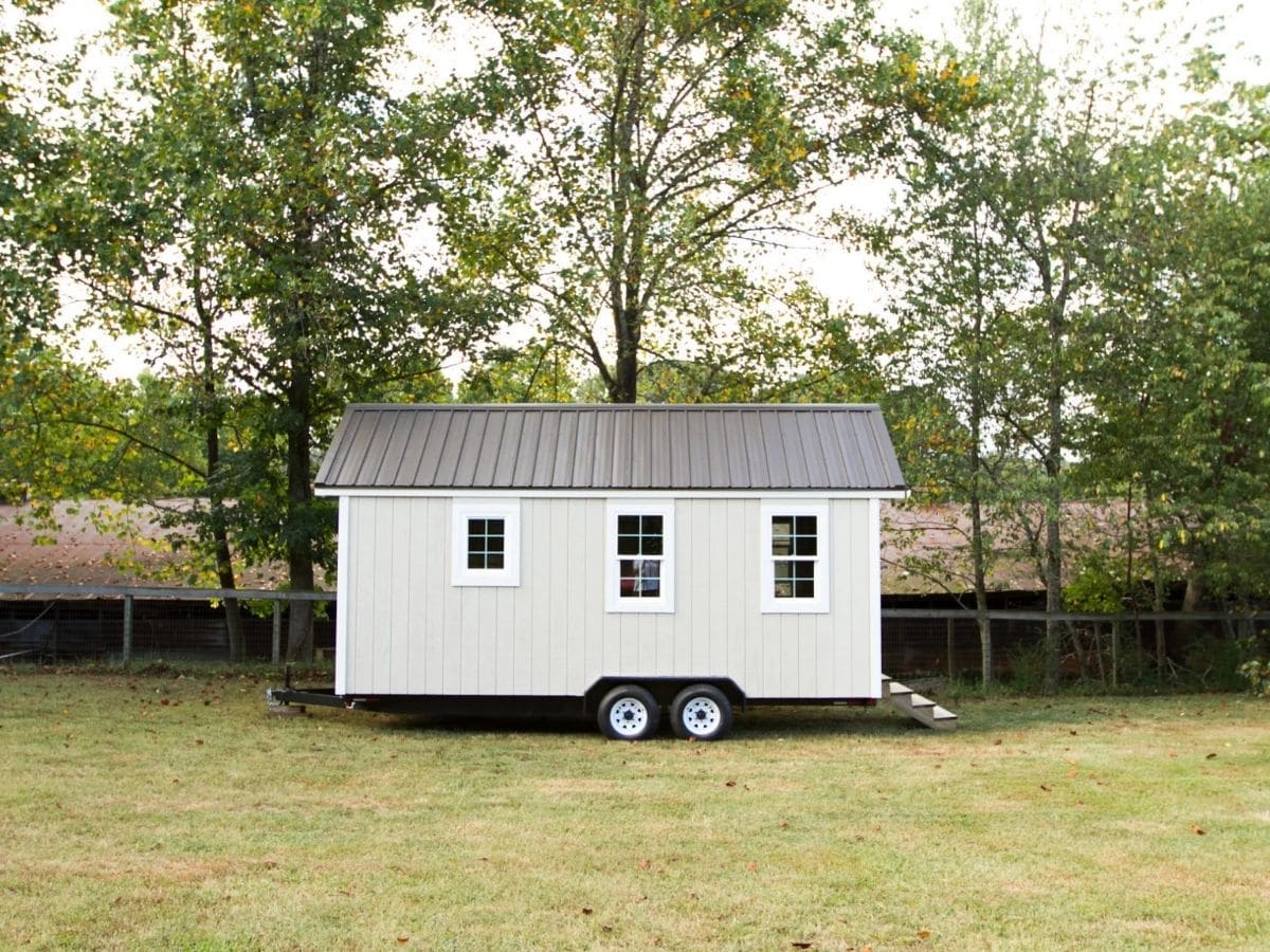 Side of tiny home on wheels with white siding