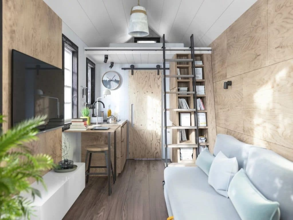 White sofa on right and television on left through door of tiny home