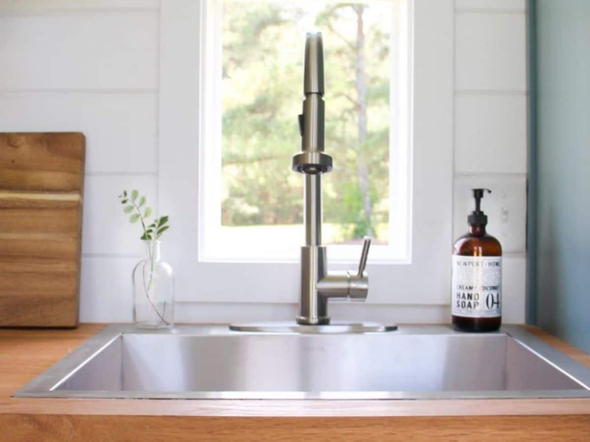 Deep stainless steel sink in butcher block counters by white shiplap walls