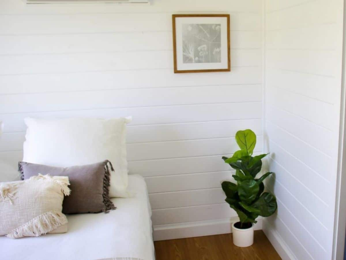 Bed against white wall with potted plant in corner under picture