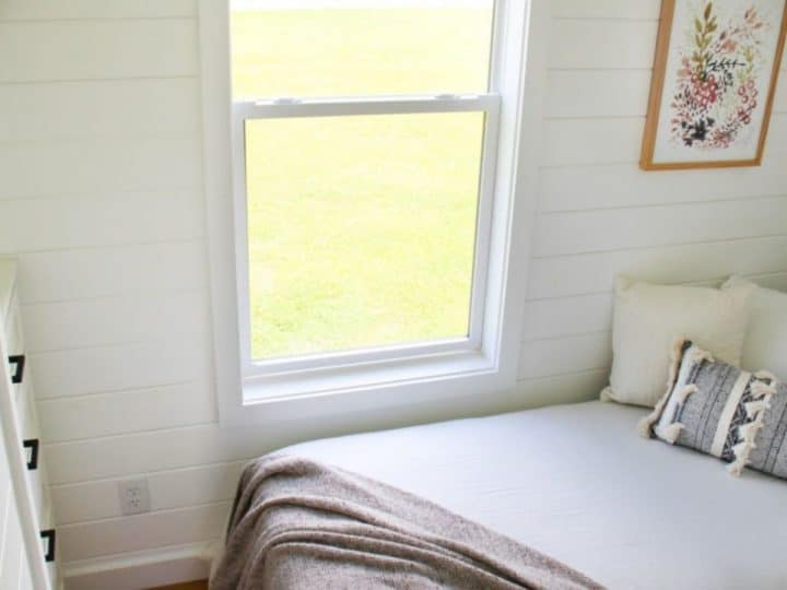 Window at end of bed in small bedroom with white walls