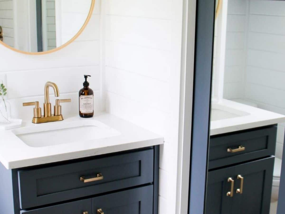 Dark blue cabinets under white sink with gold faucet