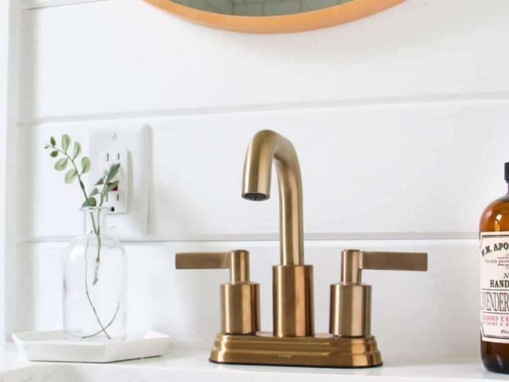 Brass faucet in bathroom next to white shiplap wall
