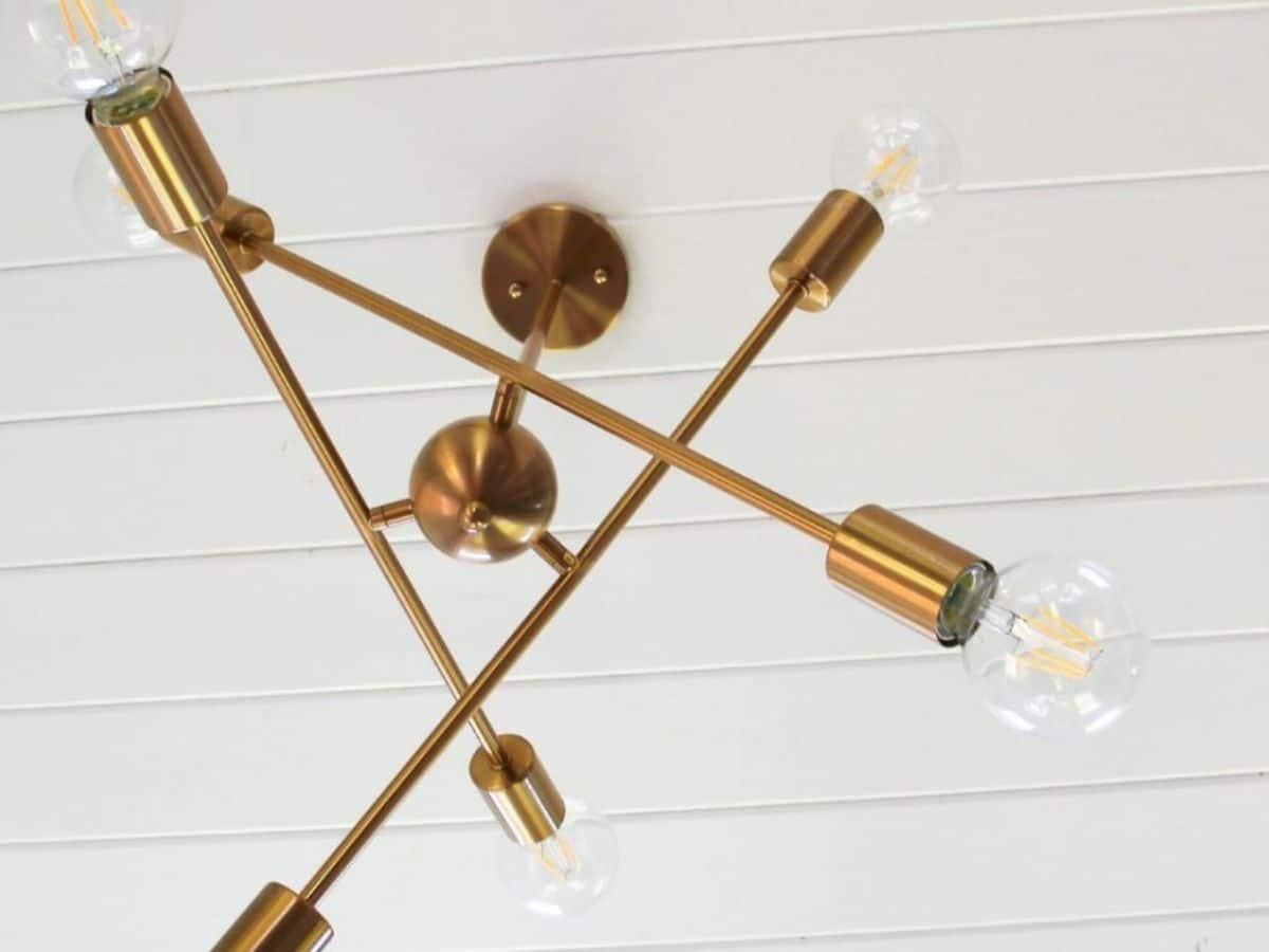 Brass artistic light fixture against white ceiling