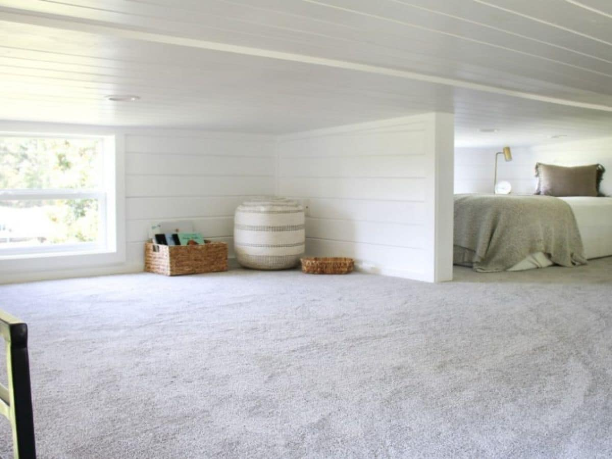 Open carpeted space in loft with storage bins in corner