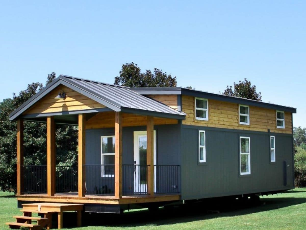 Tiny home on wheels with charcoal siding and wood accents with porch